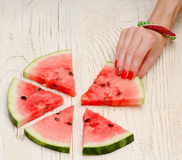 Dreieckige stücke der hände der wassermelone und der frau mit einer maniküre auf einem hellen hölzernen Premium Fotos