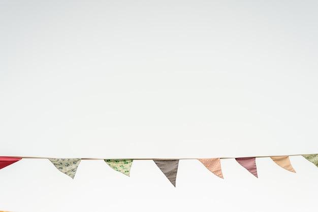 Dreieckige wimpel der weinlese, die mit dem blauen himmel im hintergrund hängen. Premium Fotos