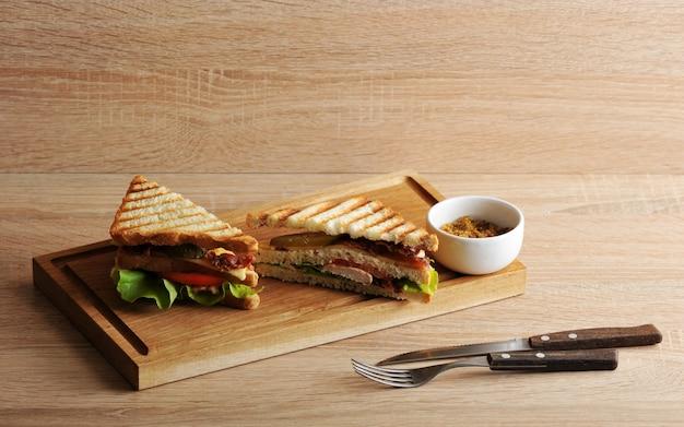 Dreieckiges sandwich zwei mit dem speck und hühnerbrust auf einem hölzernen brett Premium Fotos