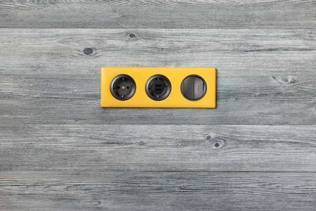 Dreifacher heller gelber rahmen mit steckdose, usb-anschlüssen und hellem schlüsselschalter auf grauer hölzerner wand. Premium Fotos