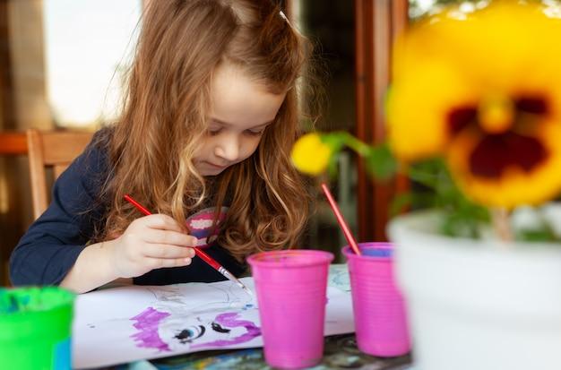 Dreijähriges mädchen malt mit aquarellen auf der terrasse. Premium Fotos