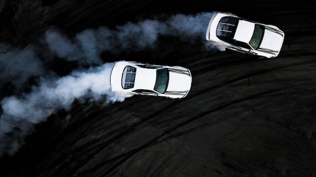 Drifting battle der draufsicht der luft zwei auf rennstrecke, zwei autos kämpfen drift, rennwagenansicht von oben. Premium Fotos