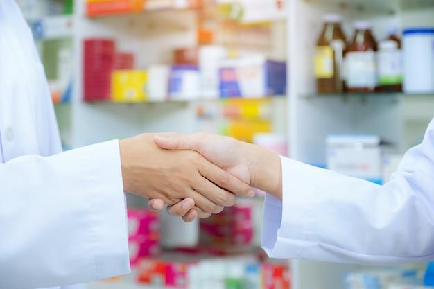 Drogerie des apothekers hände mit einem kunden an der apotheke, gesundheitskonzept rüttelnd Premium Fotos