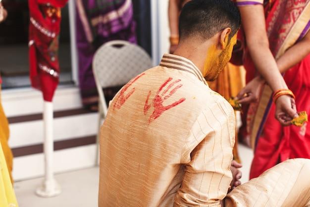 Drucke von roten palmen setzten über das hemd des indischen bräutigam-sitzens Kostenlose Fotos