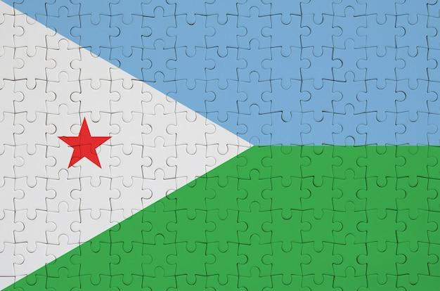 Dschibuti-flagge wird auf einem gefalteten puzzlespiel dargestellt Premium Fotos