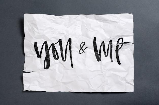 Du und ich. handgeschriebener text auf weißem zerknittertem papier. Premium Fotos