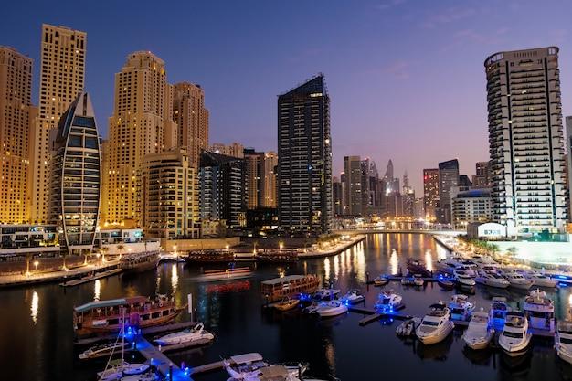 Dubai marina mit booten und gebäuden in der nacht, vereinigte arabische emirate Premium Fotos