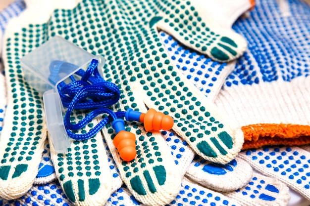 Dünne arbeitshandschuhe mit grünen pickeln und ohrstöpseln schließen oben Premium Fotos
