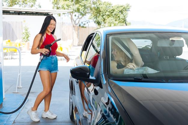 Dünne asiatische frau, die gasdüse hält und zu den freunden im auto lächelt Kostenlose Fotos