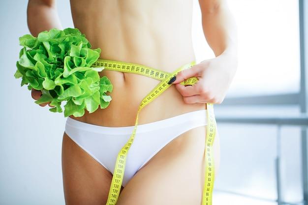 Dünne frau, die im handfrischen grünen salat hält. Premium Fotos