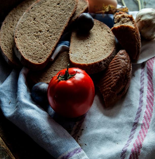Dünne geschnittene draufsicht des schwarzbrots über ein weißes tuch mit tomate und pflaume. Kostenlose Fotos