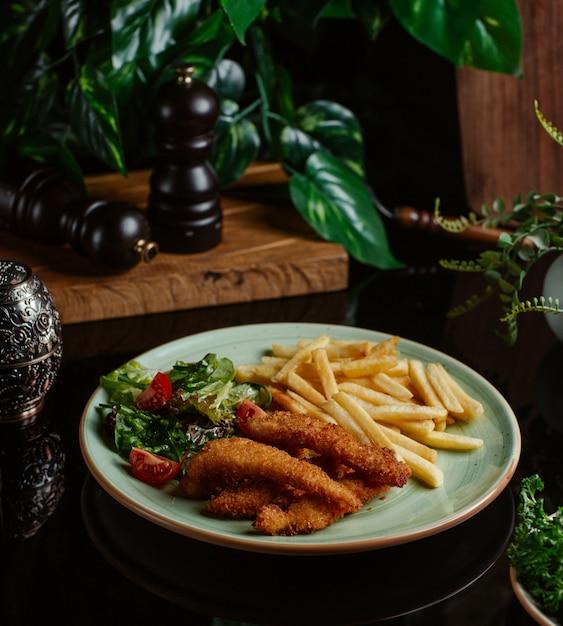 Dünne hühnernuggets mit pommes frites und veganem salat. Kostenlose Fotos