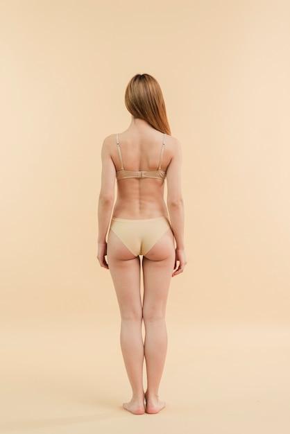 Dünne rothaarigefrau mit dem langen haar, das in der unterwäsche aufwirft Kostenlose Fotos