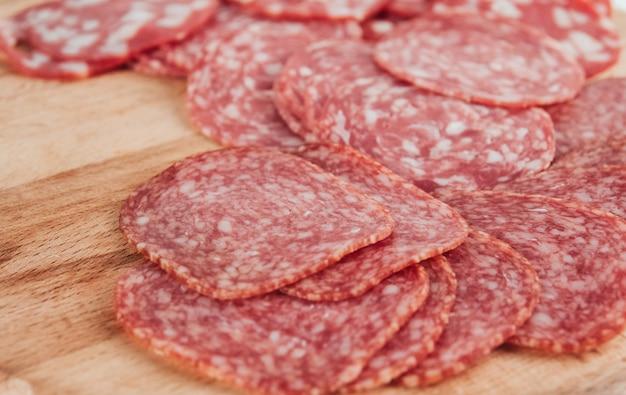 Dünne wurstscheiben auf einem holzbrett kopieren platz. in scheiben geschnittene salami. Premium Fotos