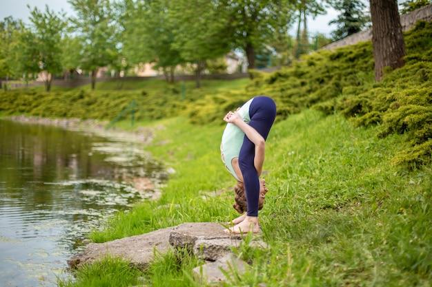 Dünner junger brunettemädchenjogi tut schwierige yogaübungen auf dem grünen gras vor ort des wassers Premium Fotos