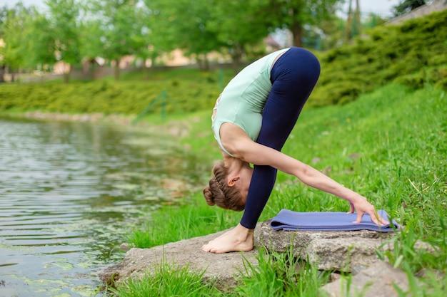 Dünnes brunettemädchen spielt sport und führt die schönen und hoch entwickelten yogahaltungen in einem sommerpark durch. grüner üppiger wald und der fluss auf dem hintergrund. frau, die übungen auf einer yogamatte tut Premium Fotos