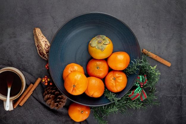 Dunkelblaue platte mit persimone und mandarinen Kostenlose Fotos