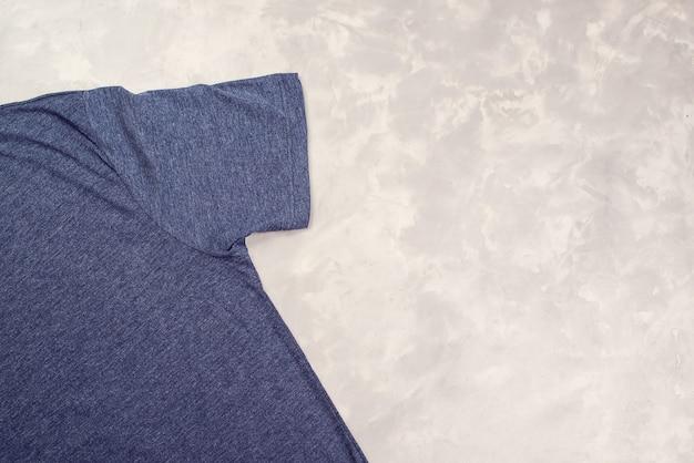 Dunkelblaues t-shirt auf grauem betonhintergrund Premium Fotos
