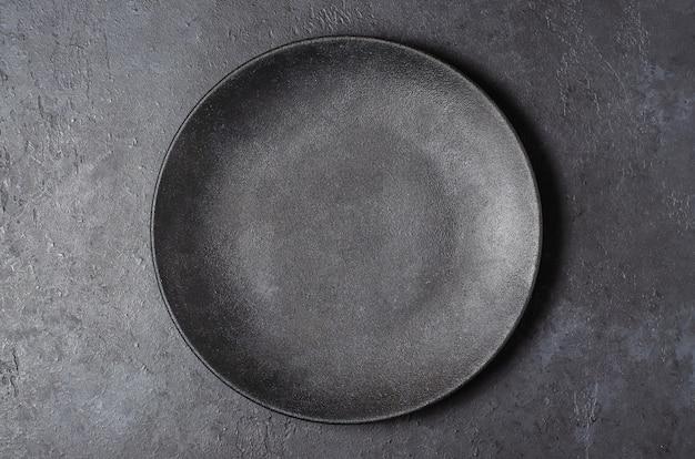 Dunkelgrauer strukturierter betonhintergrund für entwurf mit schwarzem nahrungsmittelteller. speicherplatz kopieren. Premium Fotos