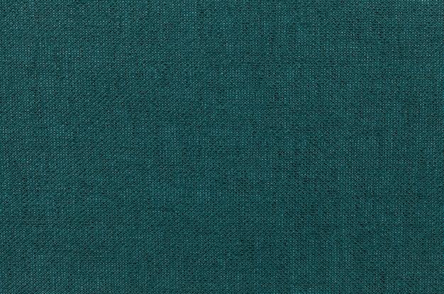 Dunkelgrüner hintergrund von einem textilmaterial. Premium Fotos