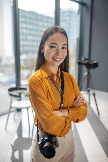 Dunkelhaariger junger süßer reporter, der glücklich lächelnd im studio steht Premium Fotos