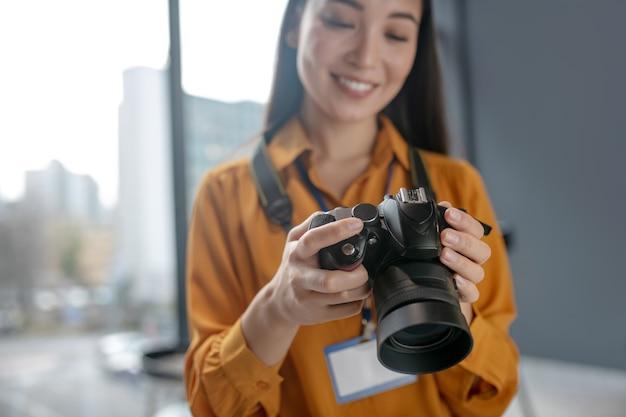 Dunkelhaariger junger süßer reporter, der lächelt, während er fotos in der kamera überprüft Premium Fotos