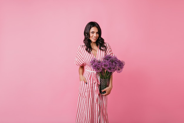 Dunkelhäutige frau souverän im rosa raum. dame im langen sommerkleid hält blumenvase. Kostenlose Fotos