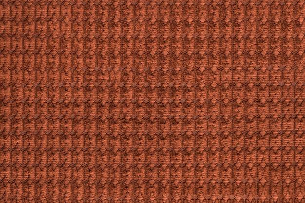 Dunkeloranger hintergrund vom weichen flauschigen gewebeabschluß oben. textur von textilien makro Premium Fotos