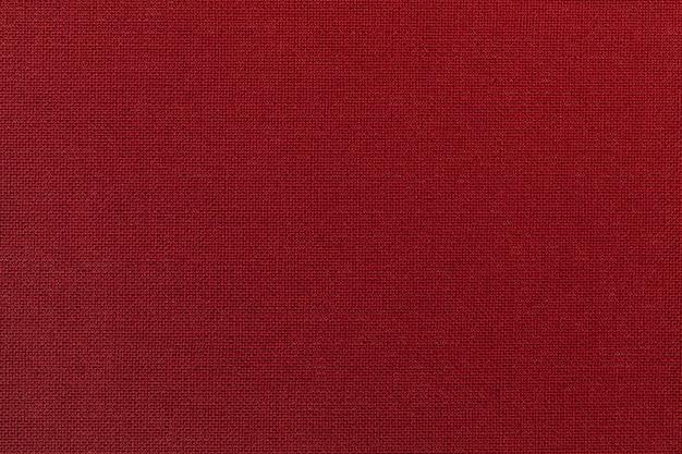 Dunkelroter hintergrund von einem textilmaterial. stoff mit natürlicher textur. hintergrund. Premium Fotos