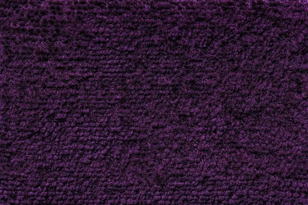 Dunkelvioletter flauschiger hintergrund aus weichem, flauschigem stoff. beschaffenheit der textilnahaufnahme Premium Fotos