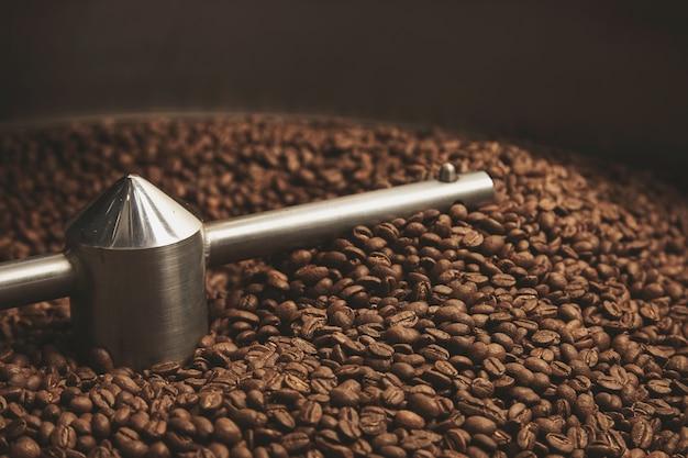 Dunkle, aromatische schokoladenkaffeebohnen, frisch gebacken und heiß, kühl im morgengrauen in der besten professionellen röstmaschine Kostenlose Fotos