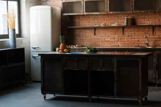 Dunkle dachbodenküche mit wand des roten backsteins. küchentisch besteck, löffel, gabeln, frühstücksobst Kostenlose Fotos