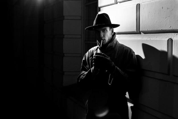 Dunkle dramatische silhouette eines mannes mit hut rauchen einer zigarette auf der straße in der nacht im noir-stil Premium Fotos