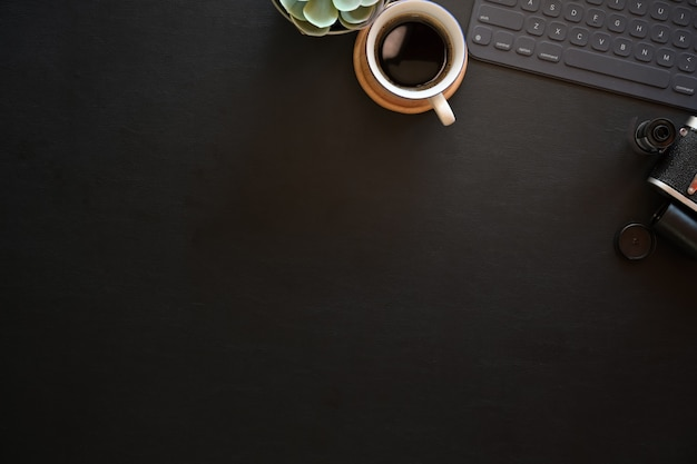 Dunkle lederne bürophotographietischtabelle mit tastaturtablette und weinlesekamera Premium Fotos