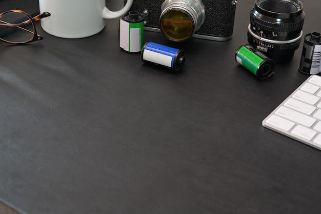 Dunkle lerther tischplatte des fotografen mit weinlesekamera, filmen, gläsern, kaffee und kopienraum Premium Fotos