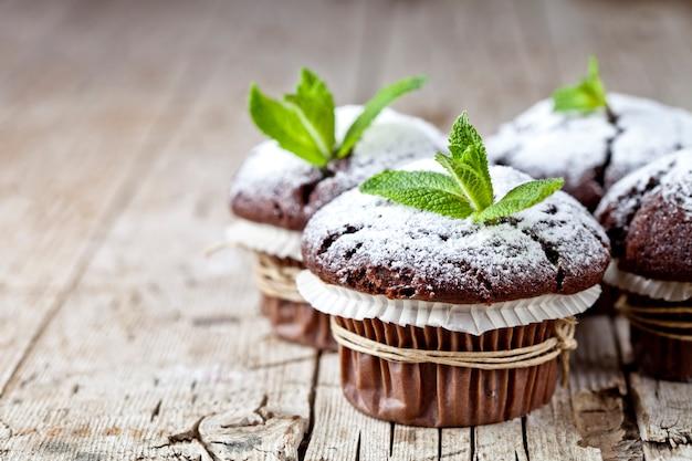 Dunkle muffins der frischen schokolade mit zuckerpulver und minze treiben auf rustikalem holztischhintergrund blätter. Premium Fotos