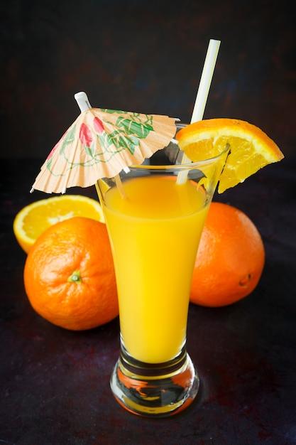 Dunkle natürliche orange frucht mit stroh und regenschirm Premium Fotos