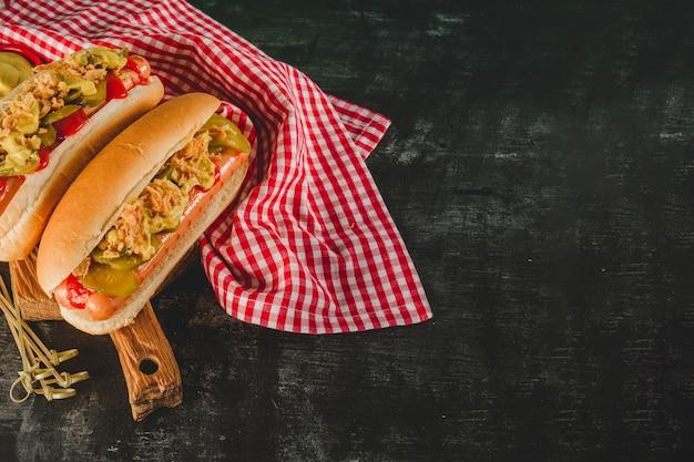 Dunkle oberfläche mit tischdecke und zwei leckeren hot dogs Kostenlose Fotos