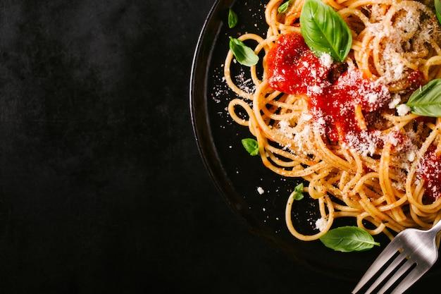 Dunkle platte mit italienischen spaghetti auf dunkelheit Premium Fotos