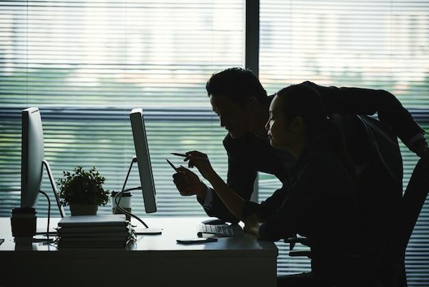 Dunkle schattenbilder von den kollegen, die auf bildschirm im büro gegen fenster zeigen Kostenlose Fotos