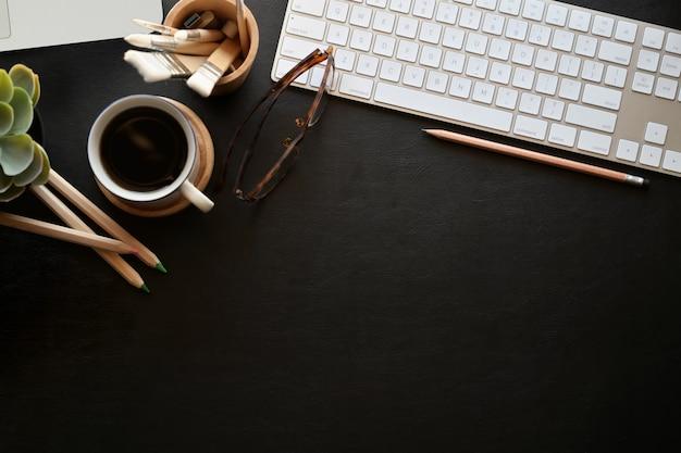 Dunkle schreibtischtischplatte des büro-leders mit tastaturcomputer, büroartikel, gläser Premium Fotos