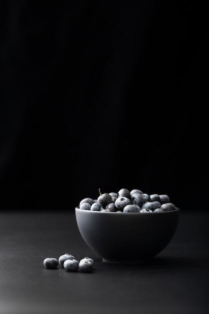 Dunkle schüssel mit moosbeeren auf einem dunklen hintergrund Kostenlose Fotos