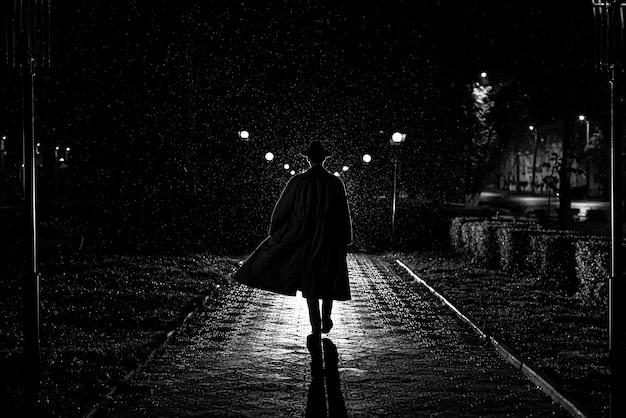 Dunkle silhouette eines männlichen detektivs in einem mantel und in einem hut im regen auf einer nachtstraße im stil von noir Premium Fotos