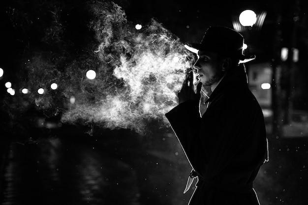 Dunkle silhouette eines mannes mit hut rauchen einer zigarette im regen auf einer nachtstraße im stil von noir Premium Fotos