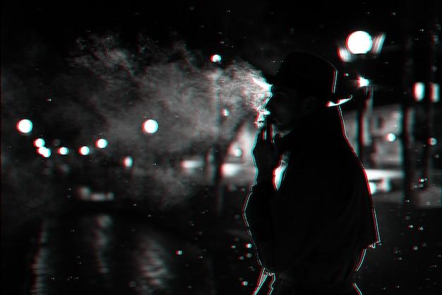 Dunkle silhouette eines mannes mit hut rauchen einer zigarette im regen auf einer nachtstraße. schwarzweiß mit 3d-glitch-virtual-reality-effekt Premium Fotos
