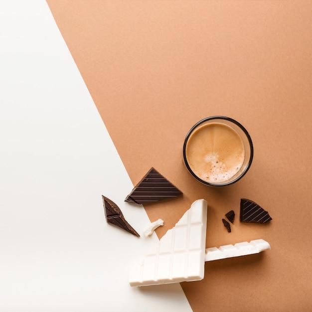 Dunkle und weiße schokoriegel mit kaffeeglas auf dual-hintergrund Kostenlose Fotos