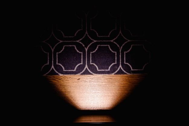 Dunkler hintergrund, der den bodenteppich durch eine lampe, kopienraum belichtet. Premium Fotos