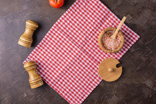 Dunkler hintergrund mit einer roten umhüllungsserviette, einem rosa salz- und pfefferrüttler mit salzrüttler. Premium Fotos