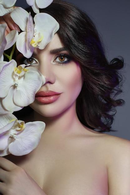 Dunkles haar des schönen mädchens und große blume nahe gesicht Premium Fotos