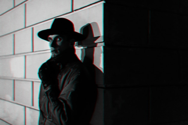 Dunkles porträt eines mannes in einem regenmantel mit einem hut nachts auf der straße. schwarzweiß mit 3d-glitch-virtual-reality-effekt Premium Fotos